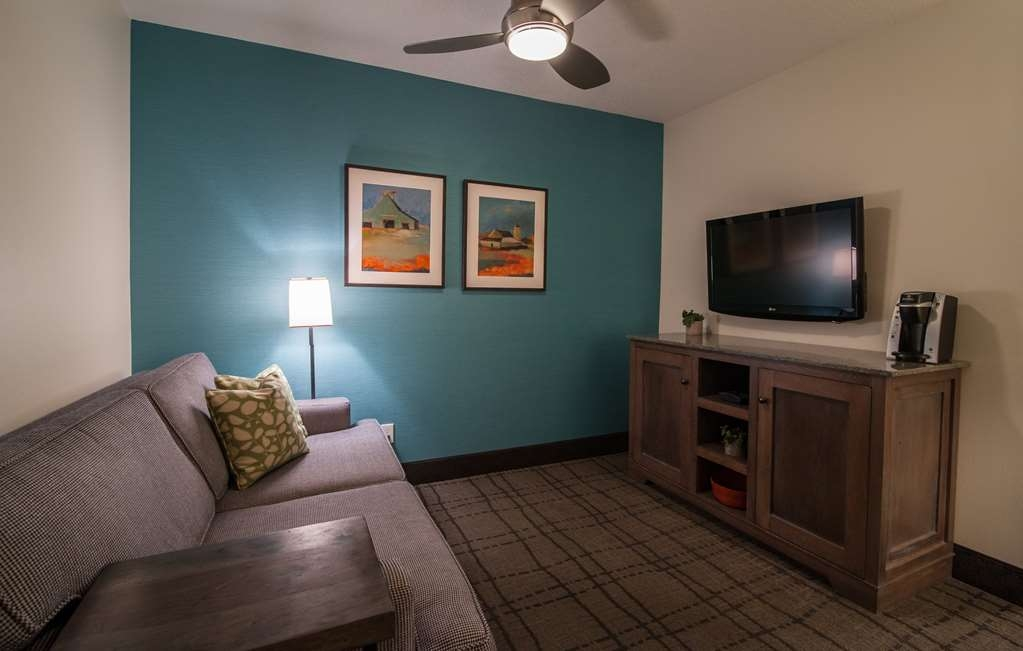 Best Western Plus University Park Inn & Suites - The living room of this suite type features a queen size sofa bed, dining table with chairs and TV.