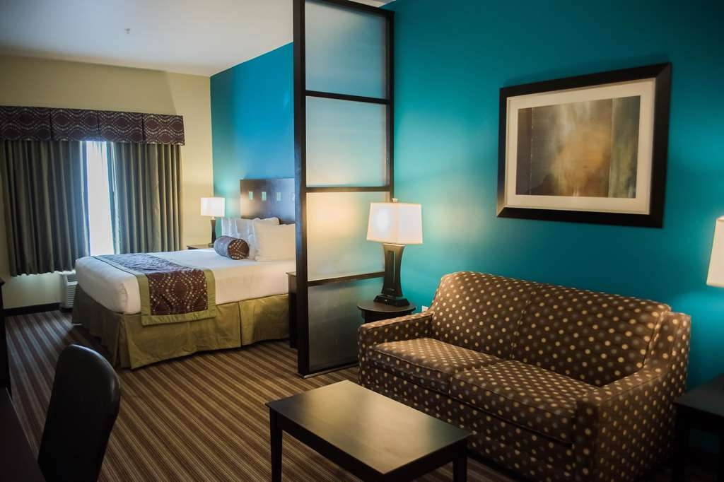 Best Western Plus DeSoto Inn & Suites - Our spacious king guest suite includes a sleeper sofa and a desk area.