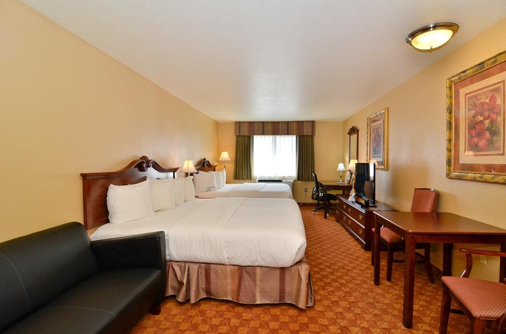 Best Western Fallon Inn & Suites - Standard two king guest room includes two king beds, leather sofa and desk.