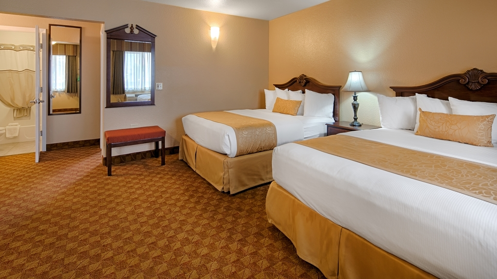 Best Western Fallon Inn & Suites - Two-room suite with two queen beds in one room and a separate living area.