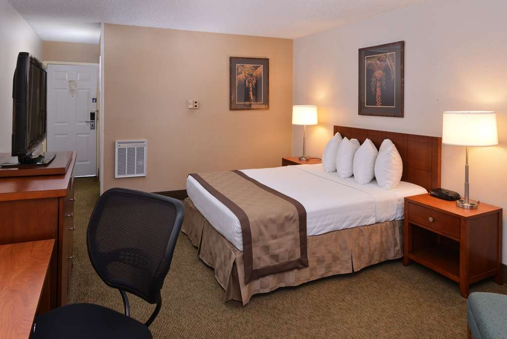 Best Western Airport Inn - Standard queen guest room featuring a 37-inch flat screen TV, easy chair and ottoman.