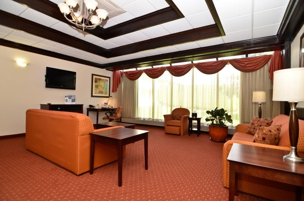 Best Western Plus Plattsburgh - The large suite living area features two sofa beds, full kitchenette, table, chairs, flat screen TV and floor to ceiling windows.