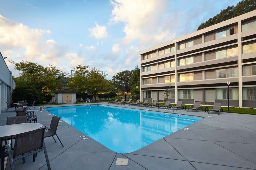 Best Western Plus University Inn - Large Outdoor Pool with Lounge Chairs and Tables for Relaxation