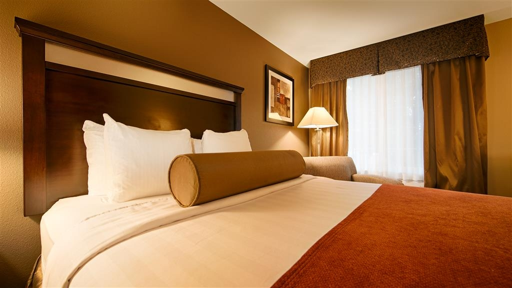 Best Western Plus Prairie Inn - One Queen Bed Guest Room with a chair and attoman