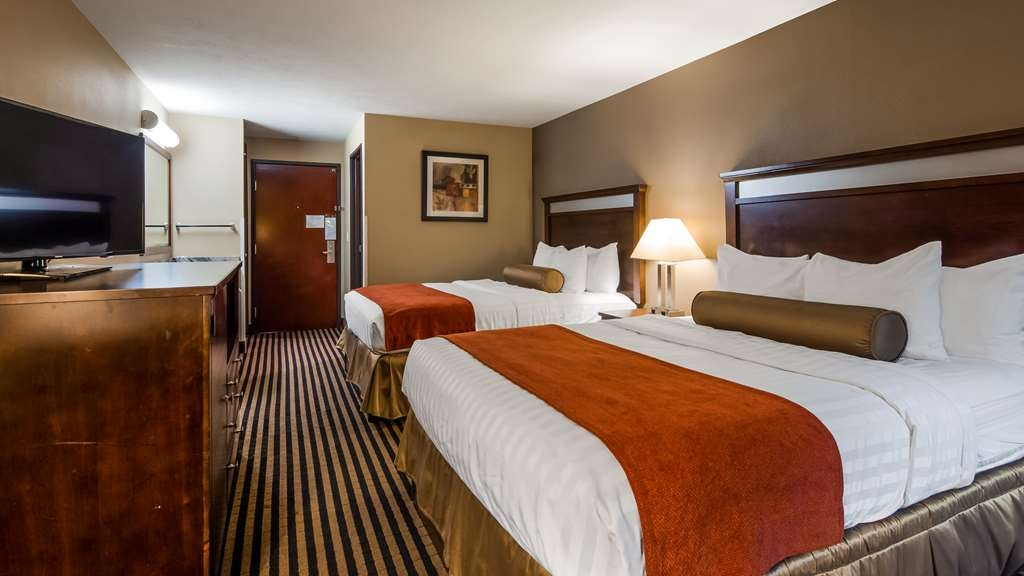 Best Western Plus Prairie Inn - Two Queen beds with a chair and ottoman.