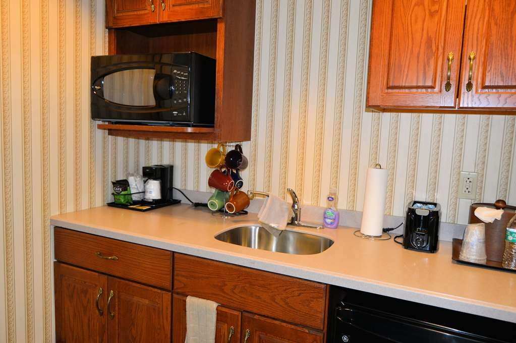 Best Western Plus Genetti Hotel & Conference Center - The Kitchenette in the Celebrity Suite is stocked with plates, glassware and silverware.