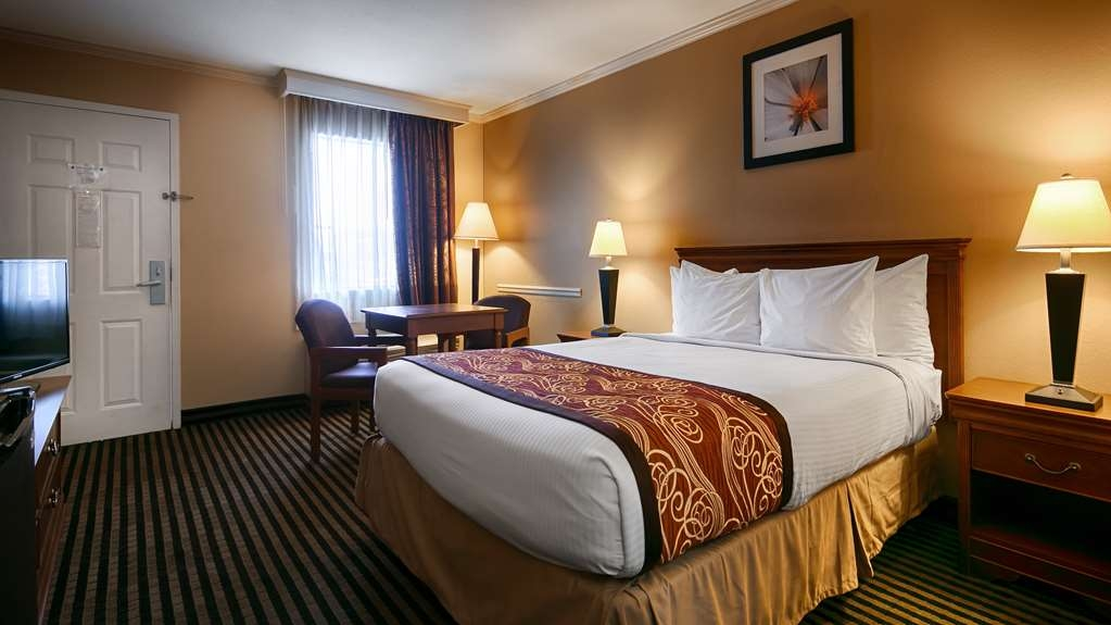 Best Western McKenzie - A guest room with a king size bed with table and chairs.