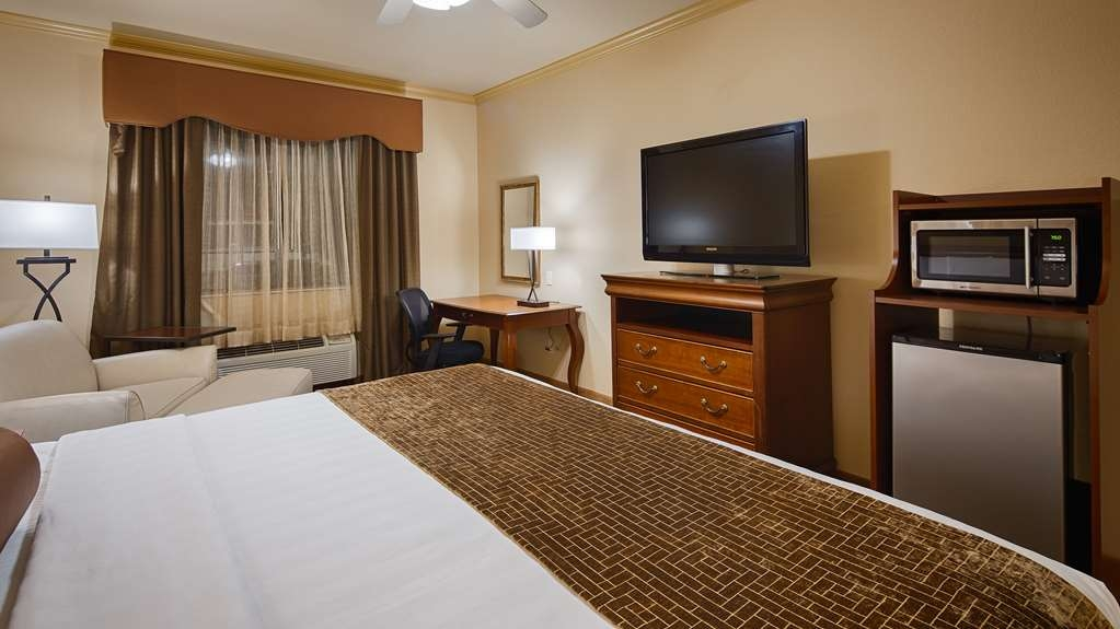 Best Western Plus Crown Colony Inn & Suites - ADA mobility king bedroom features a king bed, side chair, and bathroom with roll-in shower.