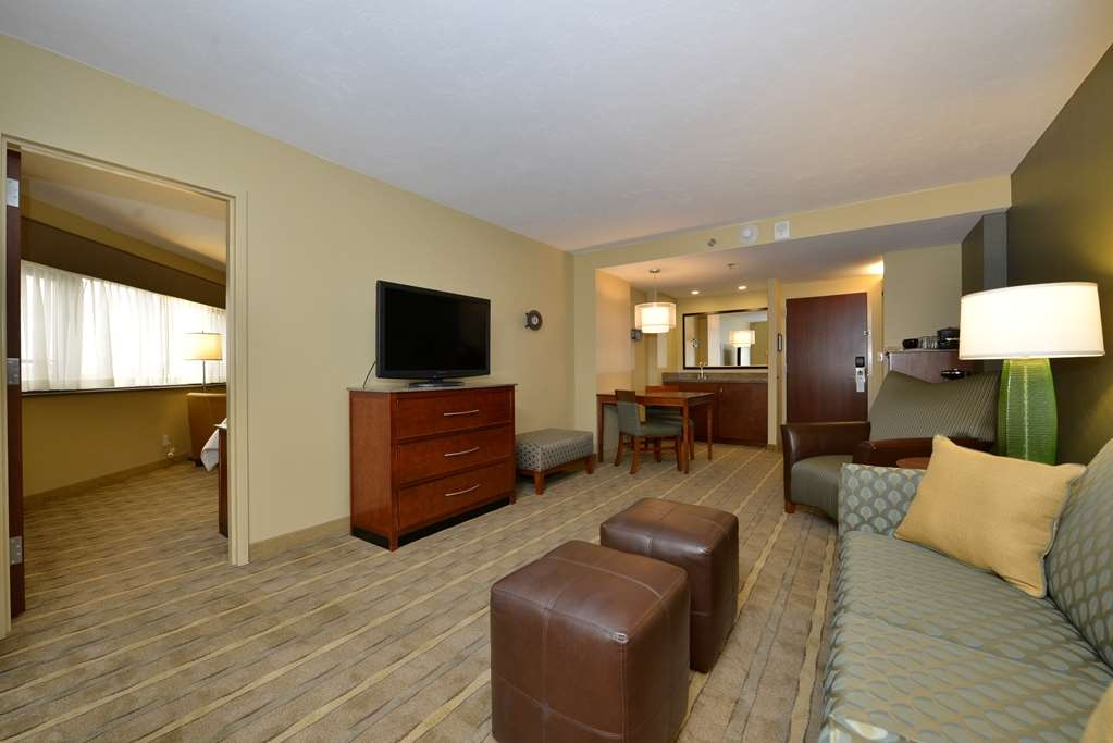 "Best Western Premier Waterfront Hotel & Convention Center - The sitting room of this two room whirlpool/fireplace suite features a wet bar, queen sofa sleeper and 42"" high definition flat screen television."