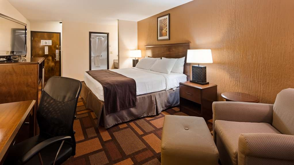 Best Western Tower West Lodge - Our deluxe king room with extra space to work at the desk or relax in the lounge chair.