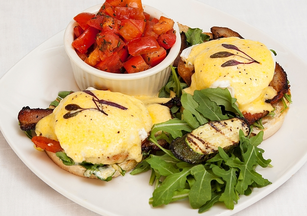 Best Western Plus Encina Inn & Suites - Live Oak Cafe Benedict with house made maple espresso bacon, roasted tomato, arugula, poached eggs, toasted sourdough and hollandaise.