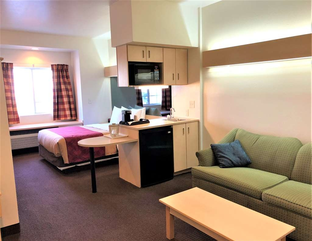 SureStay Hotel by Best Western Shallotte - Spend some time after a hectic day in the living room area featured in our queen with sofabed room.