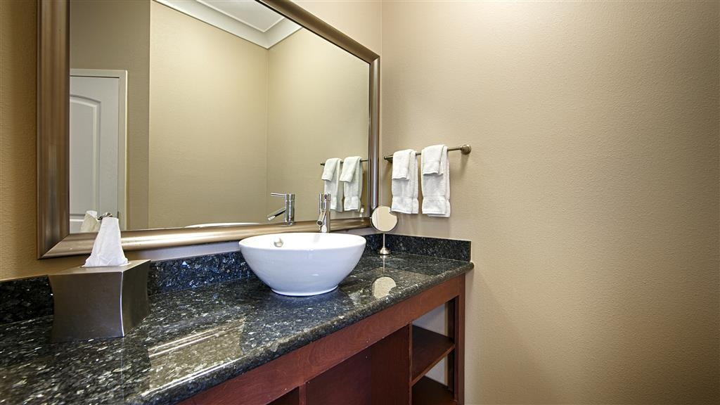 Best Western Plus Avita Suites - Guest Bathroom Blue Pearl Granite Vanity including bright lighting and Pharmacopia amenities.