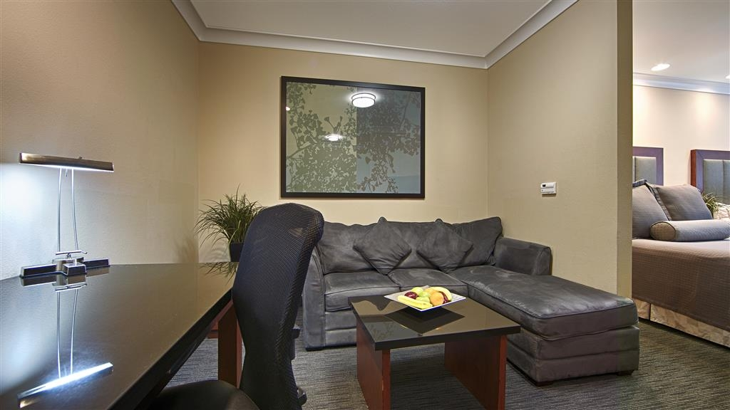 Best Western Plus Avita Suites - Studio Suite - Living room area including Wetbar, Microwave, Mini fridge, Large Work desk, Sofa w/ Chaise, and Coffee Table.