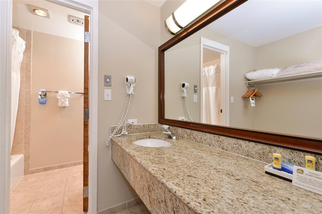 Best Western University Inn - Cuarto de baño de la suite con cama de matrimonio extragrande