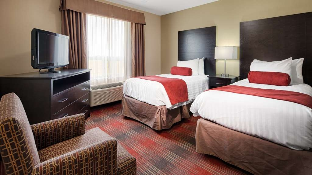 Best Western Plus Red Deer Inn & Suites - King bed with a queen pullout sofa bed and a separate bedroom that has 2 single beds