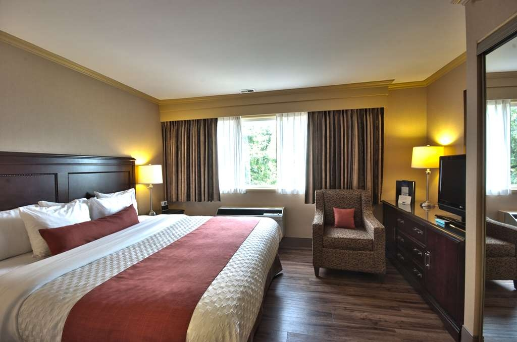 Best Western Dorchester Hotel - Enjoy luxury of our Executive Suite with a king bed in the bedroom and two pull out sofas in the living room and working desk and a parson table.