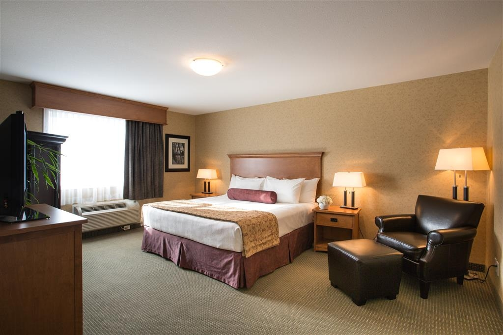 Best Western Sicamous Inn - The spacious bedroom area features a king bed, lounge chair and wardrobe.