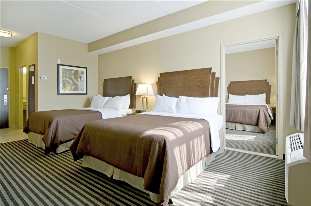 Best Western Plus Barrie - Suite familiale disposant d'une chambre avec lit queen size séparée et deux télévisions à écran plat.