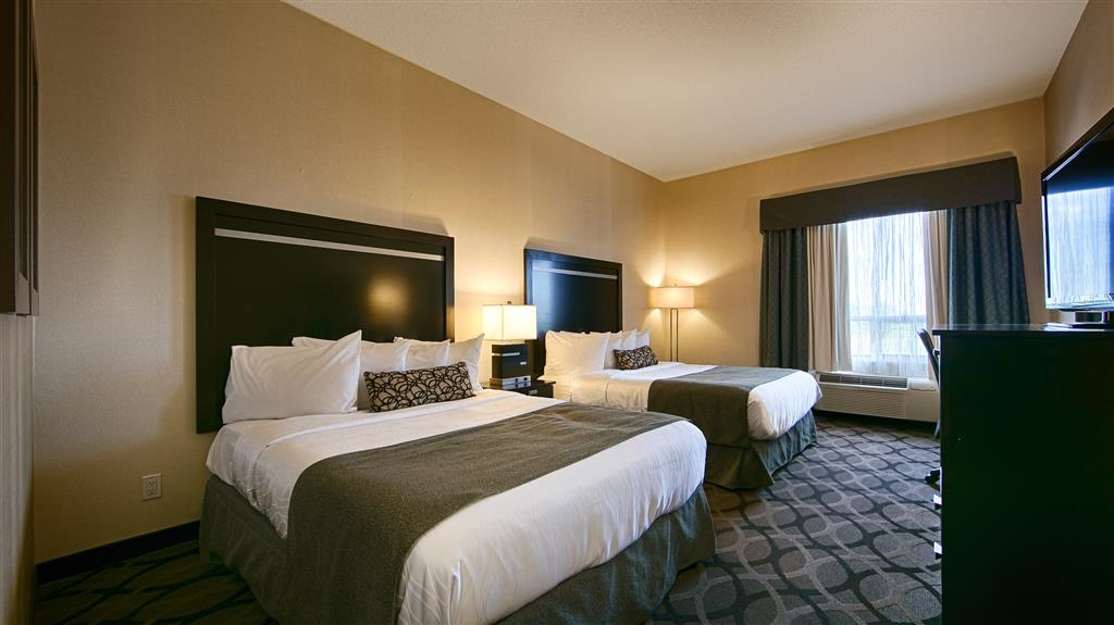 Best Western Plus Travel Hotel Toronto Airport - Two Queen Beds Guest Room contain Microwave, Refrigerator, Single cup coffee maker, Vanity Mirror, Iron & Ironing Board.