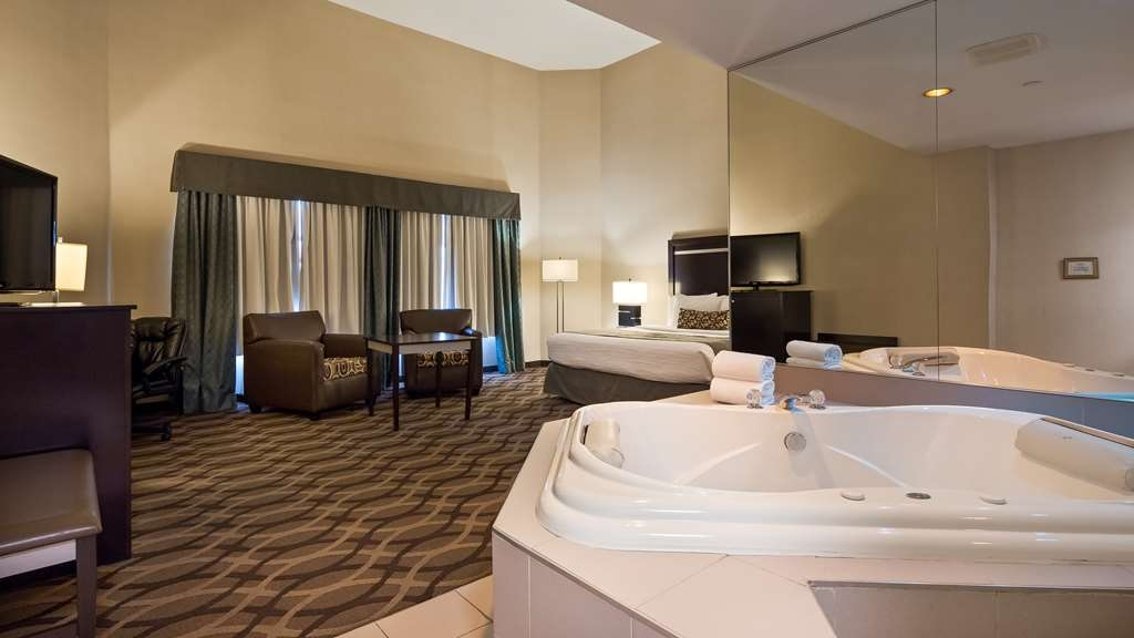 Best Western Plus Travel Hotel Toronto Airport - Jacuzzi Suite - King Bed - Guest Room contain Microwave, Refrigerator, Single cup coffee maker, Vanity Mirror, Iron & Ironing Board.