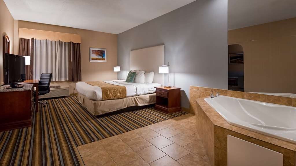 Best Western Plus New England Inn & Suites - This suite king bedroom offers distinct areas for sleeping, eating and working.