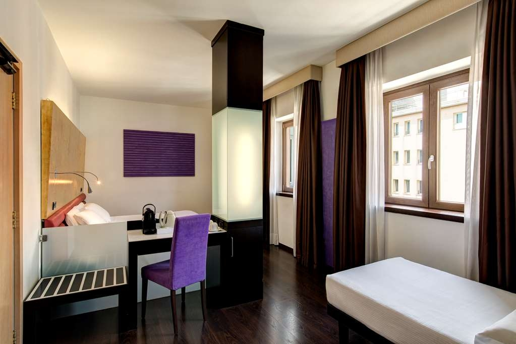 Best Western Hotel Tritone - Triple Deluxe Room: The elegant Deluxe Triple Room offer a spacious and welcoming environment furnished in a contemporary style in the tones of the violet. Up to 3 guests can sleep in the queen size bed/twin beds and in the extra bed.